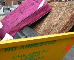 Old mattresses in a yellow skip