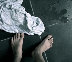 A towel and a pair of wet white feet on a tile bathroom floor